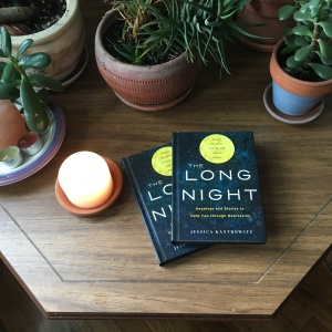 Two copies of The Long Night lying on a table with plants and candles